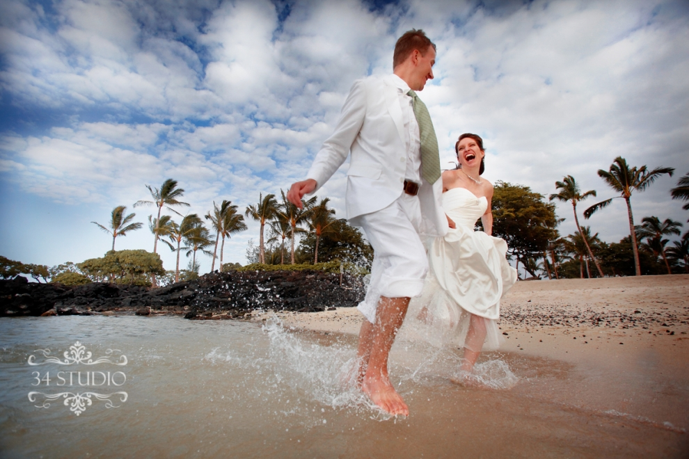 wedding couple running on the beach water splash